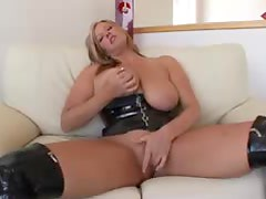 Busty blonde in kinky leather outfit fingers herself