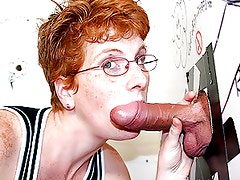 Mature redhead sucks dick through a gloryhole