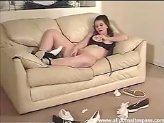 Curvy teen sits on the couch and rubs vagina