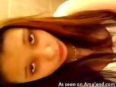 Naughty brunette solo peeing in the toilet and touching