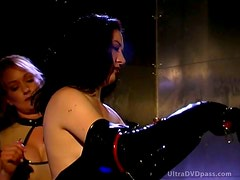 Blonde Dominatrix Orders Masochist Brunette To Put On a Sexy Latex Outfit