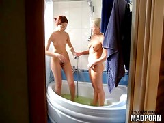 Cute teen girls laugh and soap up in bathtub