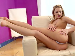 Playful girl fingers her wet pussy lying on an armchair