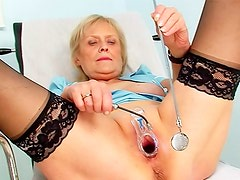 Granny in stockings and boots examines pussy