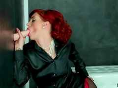 Redhead in sexy satin blouse blows a dildo