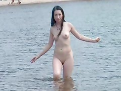 Nudist friends naked together at the beach