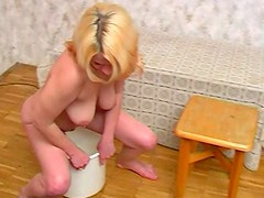 Curvy blonde pisses in a bucket