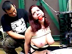 Gagged redhead bound in the dungeon