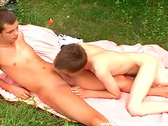 Skinny boys on a blanket suck cock outdoors