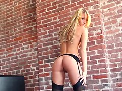 Branae Hestily poses in stockings in an apartment