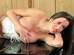 Busty tanned lady lying on piano