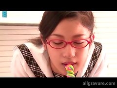 Schoolgirl in glasses licks a lollipop