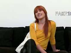 Redhead princess posing on black couch