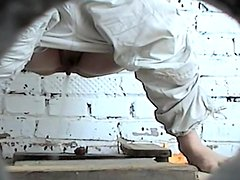 Sensual babe is pissing in the public toilet