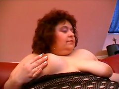 Fat mature strips and fucks toy into her vagina