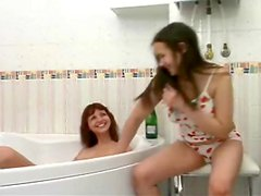 Teens wash each other in the bathtub