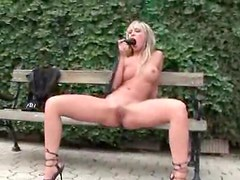 Babe sits on a bench outdoors and toys her vagina