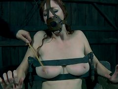 Freaky chick Holly Wildes is locked to the chair with a metal helmet on her head